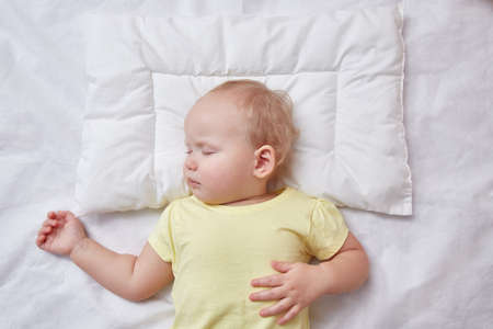 The baby sleeps on a white pillow. The view from the top