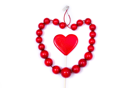 sucker: Gift for Valentines day. Red wooden beads and heart on the white background.  Stock Photo
