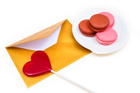 Open gold envelope, lollipop in the shape of a heart and macarons on the white background.