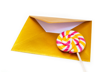 Open gold envelope and lollipop on the white background. Stock Photo