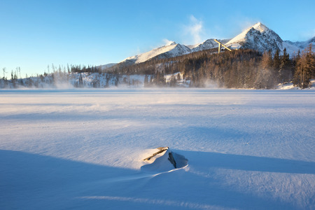 Winter view of the snowy Stbske Pleso lake surrounded by the mountains. Is a picturesque mountain lake of glacial origin and a top tourist destination in the Tatra National Park, Slovakia.