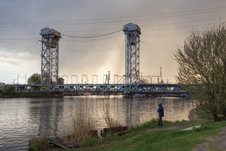 Fisherman near steel double-deck drawbridge over the Pregolya River in Kaliningrad (Konigsberg), Russia. The bridge was built in the 1913-1926 and was reconstructed in 1959-1965.