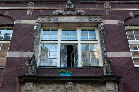 Open aged shabby window with bas-reliefs on one of the historic buildings in the Main Town of Gdansk. Poland.