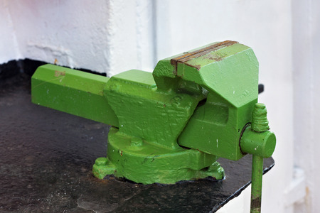 Large old green vise on the steel black table.