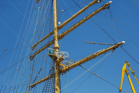 Masts of a sailing ship with the lowered sails with blue sky on the background.