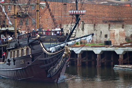 GDANSK, POLAND - JUNE 07, 2014: Wooden tourist ship stylized as a pirate boat with unknown people on the board  on the Motlawa River in the historical part of Gdansk. Publikacyjne