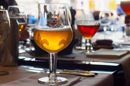LEUVEN, BELGIUM - SEPTEMBER 05, 2014: Original glass of Tripel Karmeliet beer in one of the restaurants in the Leuven. Is a golden Belgian beer with high alcohol by volume brewed by Brouwerij Bosteels Redactioneel