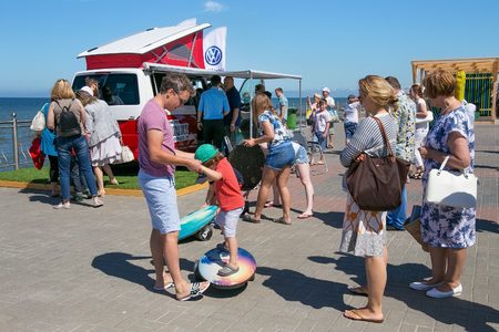 ZELENOGRADSK, KALININGRAD REGION, RUSSIA - JULY 29, 2017: Unknown tourists near modern car Volkswagen Multivan Transporter (Bulli) on the coast of the Baltic Sea in the sea resort Zelenogradsk. Stock Photo - 104747823