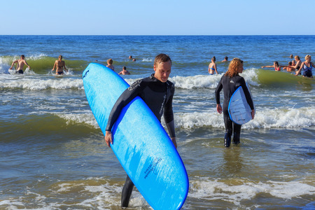 ZELENOGRADSK, KALININGRAD REGION, RUSSIA - JULY 29, 2017: Unknown surfers with surfboards standing in the blue water of Baltic Sea at summer time.