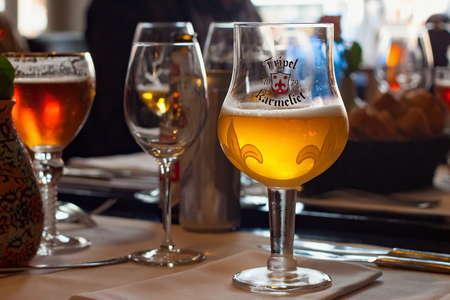 LEUVEN, BELGIUM - SEPTEMBER 05, 2014: Original glass of Tripel Karmeliet beer in one of the restaurants in the Leuven. Is a golden Belgian beer with high alcohol by volume brewed by Brouwerij Bosteels Редакционное