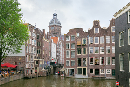 AMSTERDAM, NETHERLANDS - JUNE 25, 2017: View of the old buildings and tower of the Basilica of St. Nicholas in historical part of Amsterdam. 新聞圖片