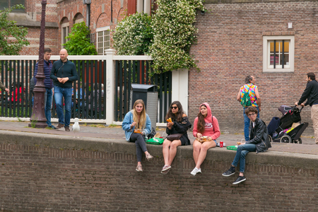 AMSTERDAM, NETHERLANDS - JUNE 25, 2017: Group of unknown young women are eating fast food on the canal banks in the historic part of Amsterdam.