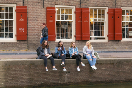AMSTERDAM, NETHERLANDS - JUNE 25, 2017: Group of unknown young women are smoking marijuana on the canal banks in the historic part of Amsterdam. Editorial