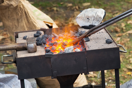 Hammer on the brazier in the street forge workshop.