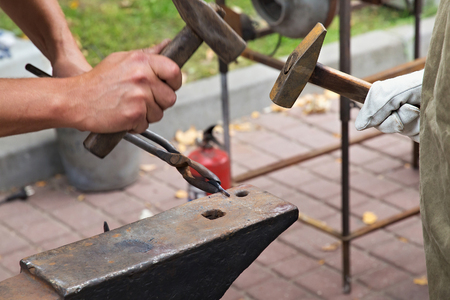 Work with hammers on the anvil in the street forge workshop.