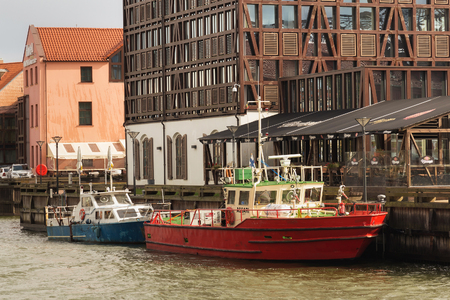 KLAIPEDA, LITHUANIA - SEPTEMBER 22, 2018: View of the embankment and old ships in the center of Klaipeda with the building known as Old Mill on the background.
