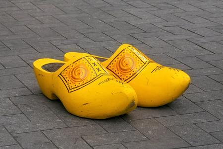 Traditional Dutch wooden big klomps (shoes also known as clogs or klompen) on the pavement  in center of Amsterdam.