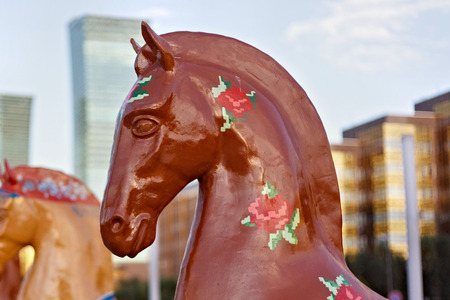 ASTANA, KAZAKHSTAN - JULY 25, 2017: Art installation with figure of horse painted in ethnic ornament in Astana on Nurzhol Boulevard with modern building on the background.