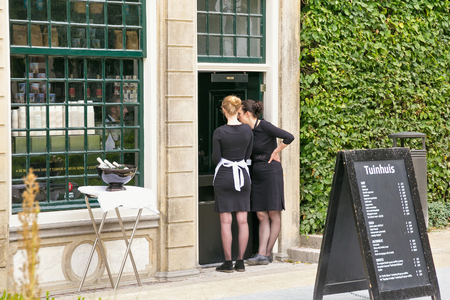 AMSTERDAM, NETHERLANDS - JUNE 25, 2017: Two unknown waitresses in black uniform dress near the Rijksmuseum Dutch national museum of arts and history in Amsterdam. 報道画像