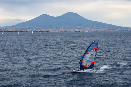 NAPLES, ITALY - OCTOBER 31, 2015: Unknown windsurfer catches the wind in the Gulf of Naples with the active volcano Vesuvius in the background.
