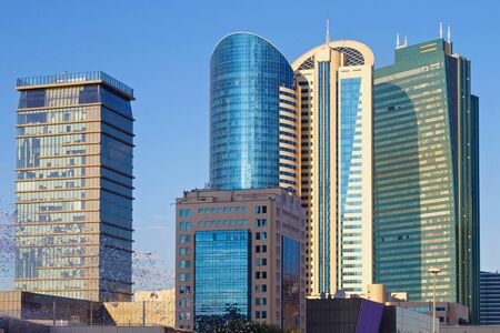 Cityscape with modern high-rise buildings with blue sky on the background.