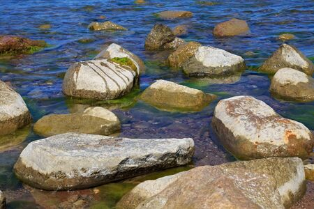 Large stones in the blue water of the sea. Stock fotó