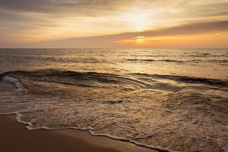 Beautiful sunset seascape with the sun and small waves.