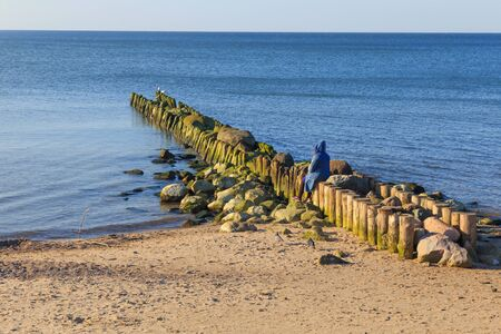 Woman sitting alone on an old breakwater and looking into the sea distance on a sunny day.