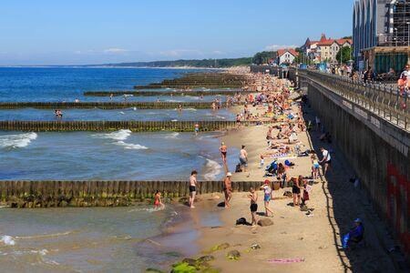 ZELENOGRADSK, REGION KALININGRAD, RUSSLAND - 18. JUNI 2019: Unbekannte Menschen ruhen auf einem Sandstrand an der Ostseeküste im berühmten Ferienort Zelenogradsk (früher bekannt als Cranz) im Sommer.