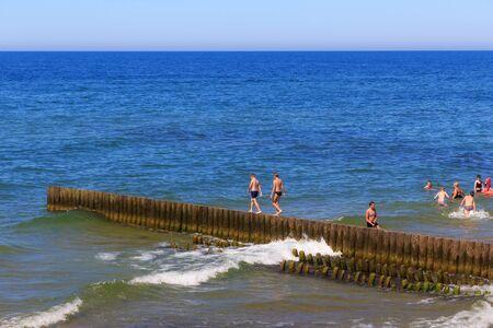ZELENOGRADSK, KALININGRAD REGION, RUSSIA - JUNE 18, 2019: Unknown people bathing near wooden breakwater on the Baltic Sea coast in famous resort Zelenogradsk (formerly known as Cranz) at summer time.