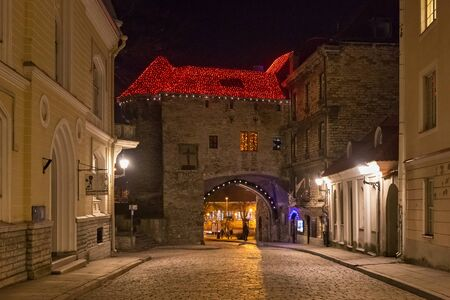 TALLINN, ESTONIA - JANUARY 12, 2018: Night winter view of the famous medieval Fat Margaret Gate with Christmas decorations in historical part of Tallinn.