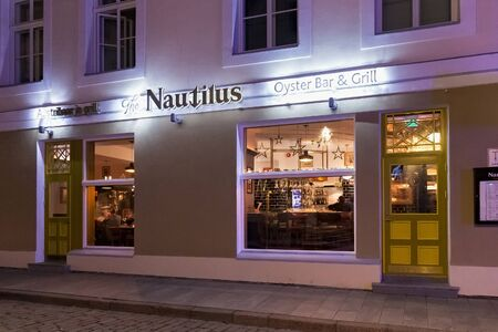 TALLINN, ESTONIA - JANUARY 12, 2018: Night winter view of the entrance to the oyster bar and grill restaurant The Nautilus in historical part of Tallinn.