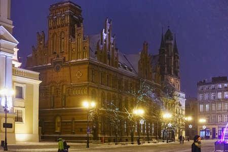TORUN, POLAND - JANUARY 08, 2016: Night view of the Old Post Office red bricks building (Poczta Polska) on the Rynek Staromiejski street in historical part of the town.