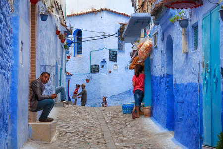 CHEFCHAOUEN, MOROCCO - MAY 28, 2017: Locals people of Medina in Chaouen. The city is noted for its buildings in shades of blue and that makes Chefchaouen very attractive to visitors.
