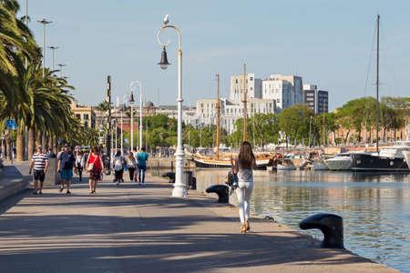 BARCELONA, SPAIN - MAY 16, 2017: Unknown people walking on the Moll de Bosch i Alsina street in Port Vell in center of Barcelona.