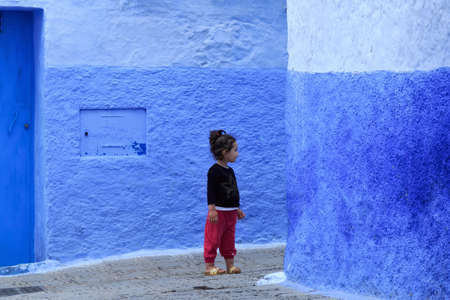 CHEFCHAOUEN, MOROCCO - MAY 28, 2017: Unknown young girl in Medina in Chaouen. The city is noted for its buildings in shades of blue and that makes Chefchaouen very attractive to visitors.