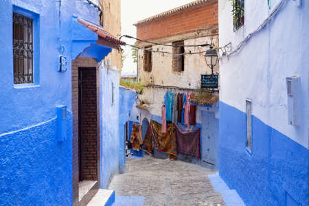CHEFCHAOUEN, MOROCCO - MAY 28, 2017: View of the walls with souvenirs in Medina in Chaouen. The city is noted for its buildings in shades of blue and that makes Chefchaouen very attractive to visitors. Редакционное