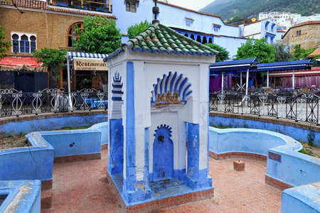 CHEFCHAOUEN, MOROCCO - MAY 28, 2017: View of the old fountain in center of Chaouen. The city is noted for its buildings in shades of blue and that makes Chefchaouen very attractive to visitors. Редакционное