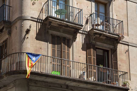 BARCELONA, SPAIN - MAY 15, 2017: View of the building in Barcelona center with blue Estelada flag on the balcony. The Estelada is an unofficial flag typically flown by Catalan independence supporters.
