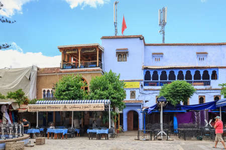 CHEFCHAOUEN, MOROCCO - MAY 29, 2017: Old buildings with cafe in the center of Chaouen. The city is noted for its buildings in shades of blue and that makes Chefchaouen very attractive to visitors.