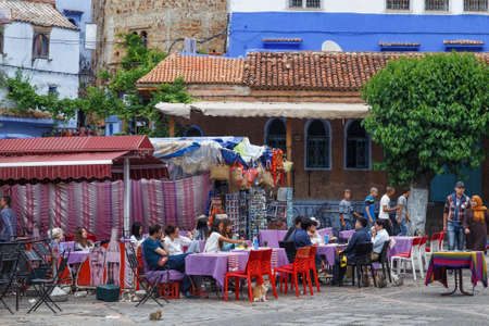 CHEFCHAOUEN, MOROCCO - MAY 28, 2017: Unknown people resting in street cafe in center of Chaouen. The city is noted for its buildings in shades of blue and that makes town very attractive to visitors. Редакционное