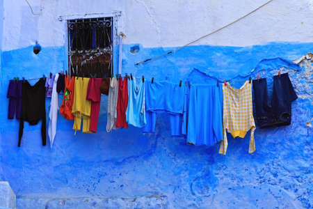 CHEFCHAOUEN, MOROCCO - MAY 29, 2017: Hanging drying clothes in Chefchaouen, Morocco. The city is noted for its buildings in shades of blue and that makes Chefchaouen very attractive to visitors.