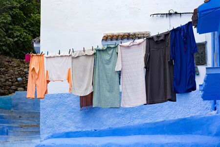 Hanging drying clothes in Chefchaouen, Morocco. The city, also known as Chaouen is noted for its buildings in shades of blue and that makes Chefchaouen very attractive to visitors. Фото со стока