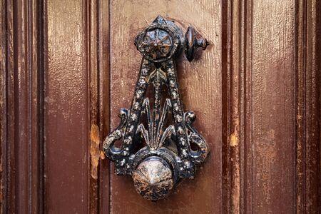Old shabby vintage metal door knocker in the wooden door. Imagens