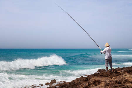 Unknown fisherman on the Atlantic Ocean coast in sunny day.