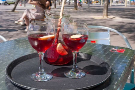 Jug and glasses with sangria beverage on the table in street cafe in center of Barcelona. Spain.