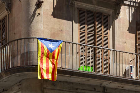 View of the historic building in Barcelona center with blue Estelada flag on the balconies. The Estelada is an unofficial flag typically flown by Catalan independence supporters. Spain.