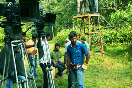 team from behind: KODAIKANAL, INDIA - JUNE 21, 2016: Video camera operator on nature background, film shooting spot