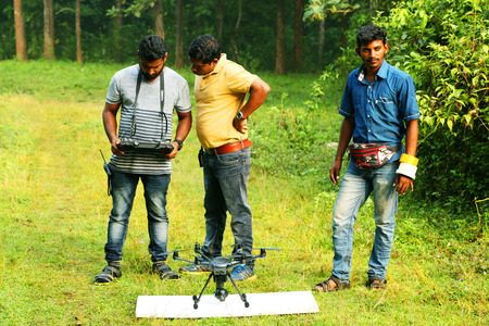 KODAIKANAL, INDIA - JUNE 21, 2016: Young man with two assisted photographer is shooting video with radio controlled quadcopter, Young male is taking photo on flying remote camera during summer trip