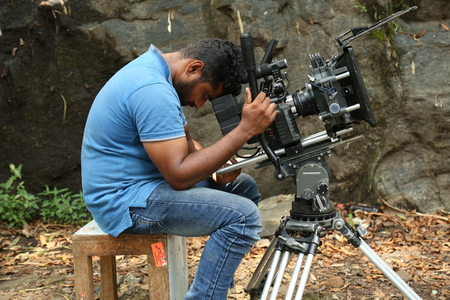 KODAIKANAL, INDIA - JUNE 29TH, 2015: Look out from the camera, camera man sleep in the shooting spot.